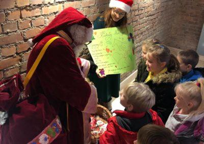 Dzieci biorą cukierki od Mikołaja