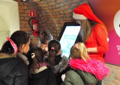 Mikołajka pokazuje dzieciom coś na ekranie