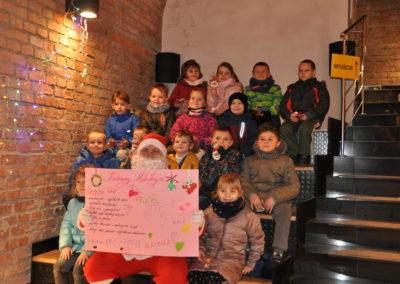 Grupa dzieci siedzi z Mikołajem