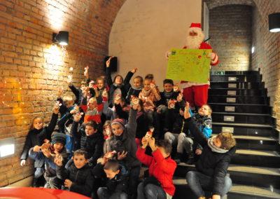 Dzieci pozują z prezentami i Mikołajem