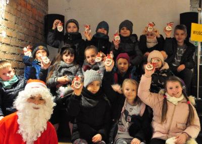 Dzieci z prezentami i Mikołajem