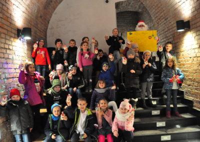 Grupa dzieci z Mikołajem w podziemiach